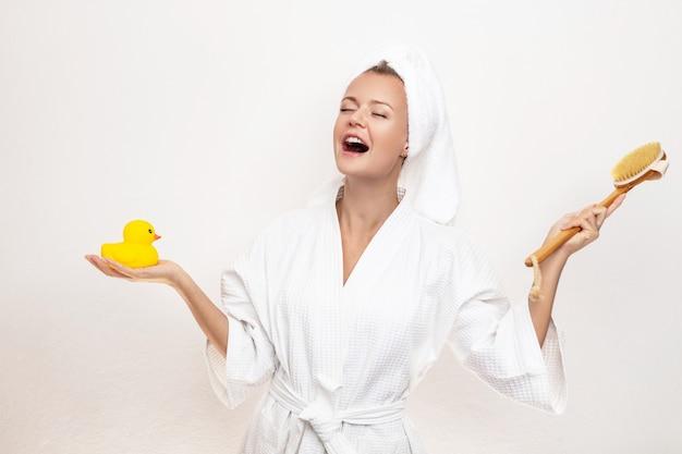 Симпатичная красивая девушка в халате и полотенце на голове позирует петь песни на белом с маленькой желтой резиновой уткой в одной руке и кистью для тела в другой руке.