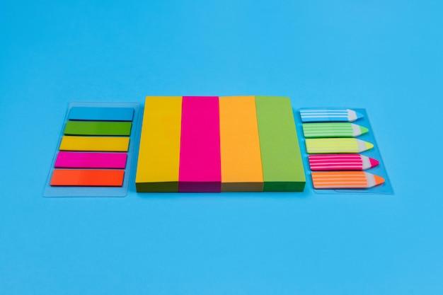 Наборы ярких цветных наклеек в виде полосок желтого, розового, оранжевого, зеленого цвета расположены по синему, рядом с которым расположены наклейки в виде полосок и карандашей. место для рекламы.