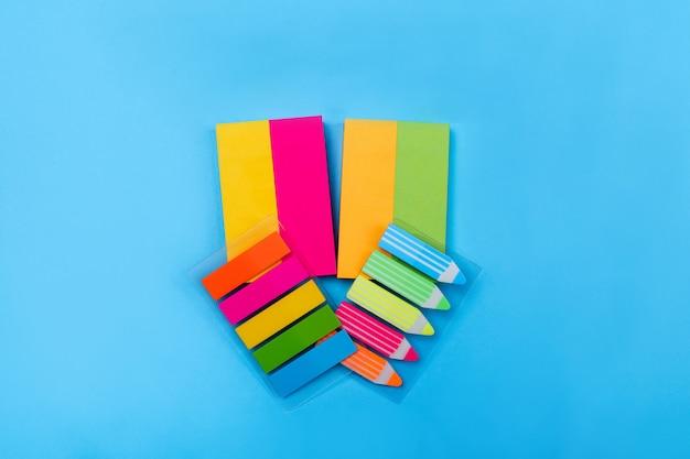 Наборы ярких цветных наклеек в виде полосок желтого, розового, оранжевого, зеленого цвета расположены по синему цвету, рядом с которым расположены наклейки в виде полосок и карандашей по центру. крупный план.