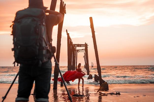 Фотограф с рюкзаком снимает барышню в длинном красном платье под старым недостроенным мостом на закате.