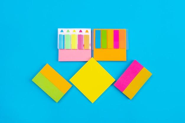 Несколько цветных наборов наклеек желтого, розового, оранжевого цвета с наклейками в виде карандашей и полосок расположены по центру на синем. крупный план. наборы для заметок. канцтовары.