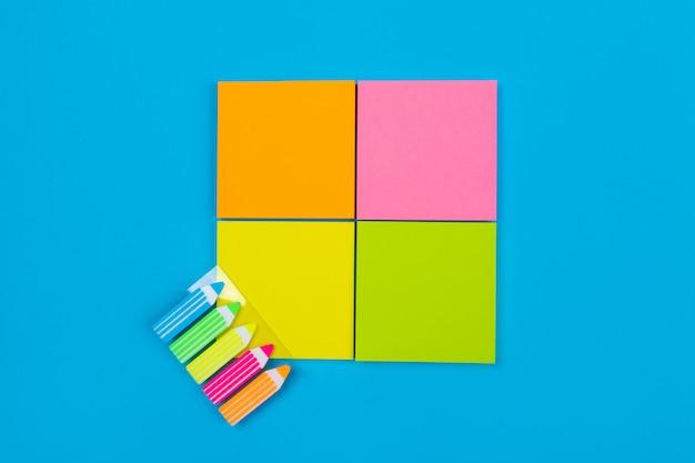 Четыре маленьких набора желтых, оранжевых, розовых, зеленых наклеек, сложенных в квадрат на синем, рядом с которым находятся наклейки в виде карандашей. крупный план. место для заметок.