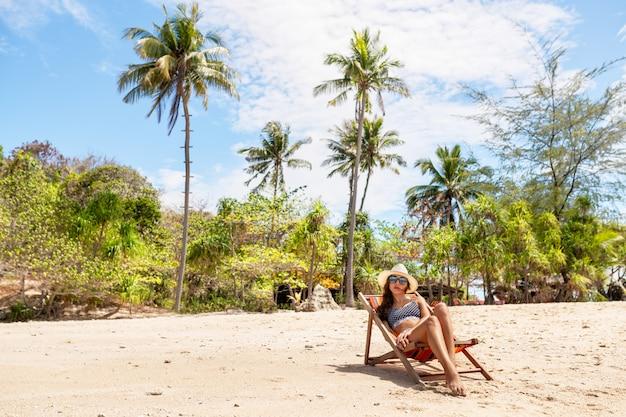 Красивая девушка на шезлонге в бикини. тропический отдых.
