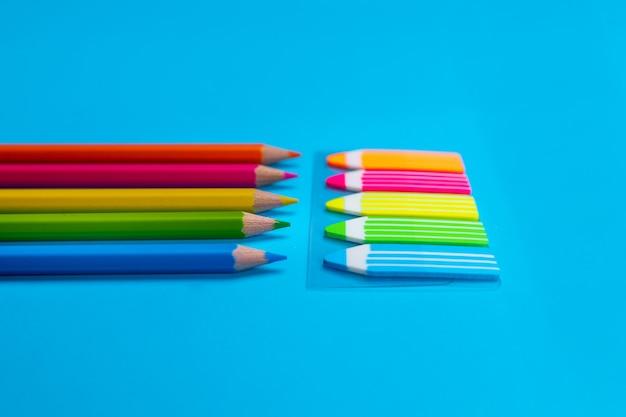 Яркие наборы карандашей желтого, оранжевого, розового, зеленого, синего цвета в виде наклеек в виде карандашей на синем. крупный план.