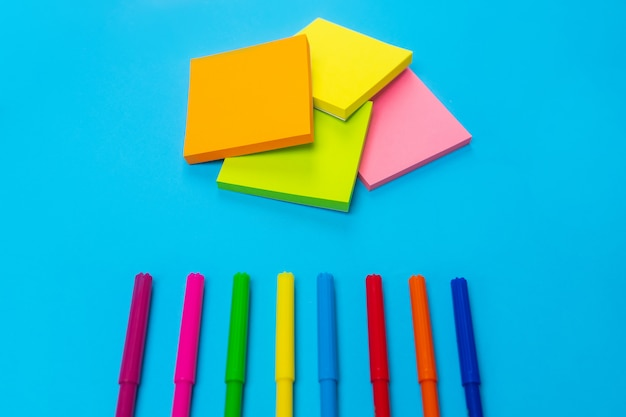 Фотография красочных ярких фломастеров, лежащих на дне синего цвета, рядом с которым находится набор желтого, оранжевого, розового, зеленого цветов. крупный план. канцтовары. вид сверху.
