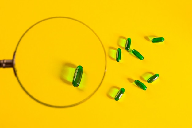 Несколько зеленых прозрачных капсул выложены на желтый под увеличительным стеклом. здоровье. фармакология.