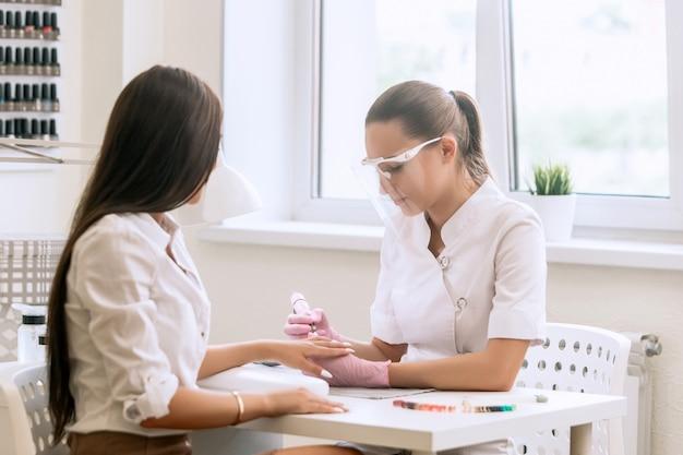 モダンなビューティーサロンで女性のクライアントにマニキュアをしているマスクのネイリストの女性