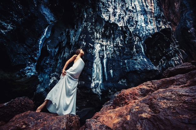 長い白いドレスを着た謎の少女-白人モデルが黒い岩の間を歩きます。ハロウィーンのゴシックフォトセッションテーマ。珍しい、創造的な衣装