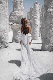 Загорелая стройная молодая женщина с макияжем и темными волосами в длинном белом платье позирует возле белых камней. вид сзади