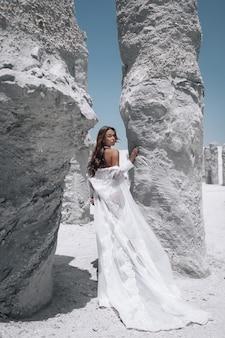 Загорелая стройная молодая женщина с макияжем и темными волосами в длинном белом плаще позирует возле белых камней. вид сзади