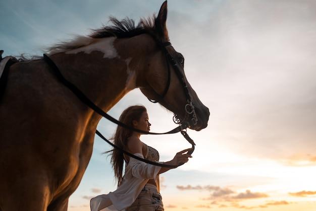 幸せなファッショナブルな若い女性がビーチで馬とポーズ
