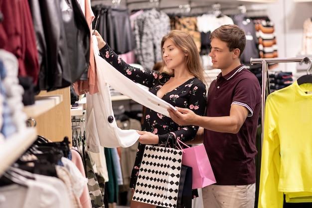 Молодая девушка помогает своему парню выбрать одежду, держа в руке белую рубашку, а парень с пакетами в руке смотрит на что-то интересно.