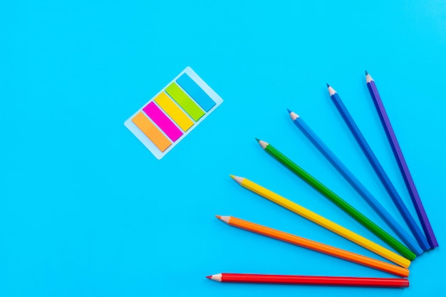 Яркие цветные карандаши выложены в виде солнца в правом углу на синей стене, в центре которой находятся цветные наклейки в виде полос