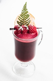 Свежий фиолетовый коктейль из фруктов и овощей для здорового образа жизни, изолированный на ярком мраморе
