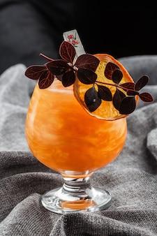 Ярко-оранжевый старомодный коктейль с виски на сером