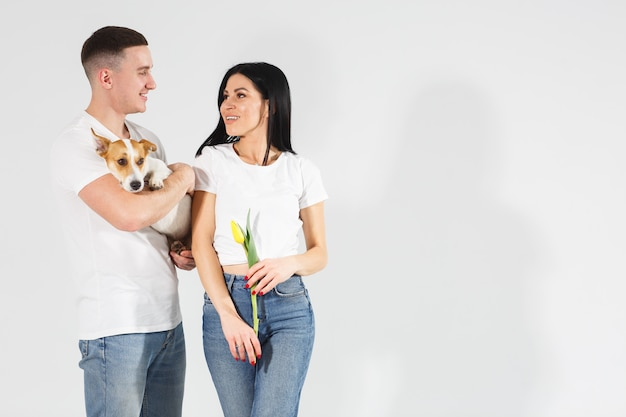 Крупным планом портрет молодая пара с желтыми цветами и собакой. прекрасная пара, обнимающаяся с мечтательным любовным выражением. счастливая собачья жизнь. милая семья. празднование женского дня.