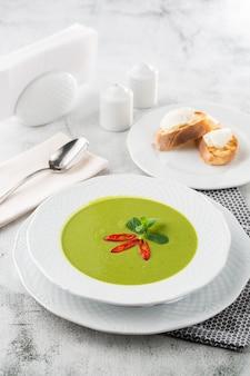 ほうれん草とブロッコリーのグリーンクリームスープ。パルメザンチーズとクルトンを追加します。白い大理石のテーブル。概念健康食品とダイエット。素朴なボウルにほうれん草のスープの新鮮な自家製クリーム。