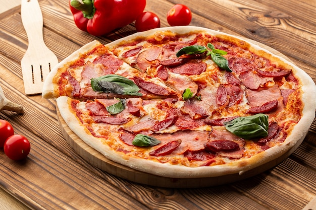 ハム、ホットソーセージ、サラミ、木製の背景にモッツァレラチーズのピザをクローズアップ。イタリア料理。生ハムとサラミの木製のテーブルのピザ。上面図。
