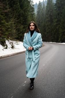 冬の山のテーブルの道を歩いてセクシーなブルネットの少女。スタイリッシュな青いロングコートを着て華やかな若い女性。ファッション、ビジネス、美しい人々のコンセプト。