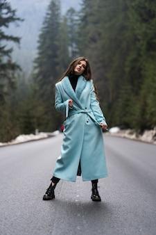 セクシーなブルネットの少女は、冬の山のテーブルの道を歩きます。スタイリッシュな青いロングコートを着て華やかな若い女性。ファッション、ビジネス、美しい人々のコンセプト。