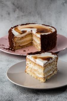大理石の背景にテーブルの上の皿に白いクリームとおいしいビクトリアスポンジケーキ。ペストリーカフェやカフェメニューの壁紙。垂直。