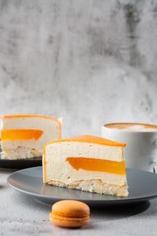 ココナッツ、パッションフルーツ、マンゴー、バナナをチョコレートの釉薬で覆ったエレガントなケーキ。大理石の背景にオレンジの層状ケーキのスライス。ペストリーカフェやカフェメニューの壁紙。垂直。