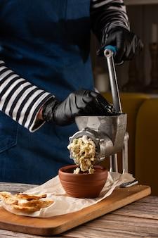 肉挽き器でテーブルの食材を使った魚のカツレツのミンチ肉を調理します。