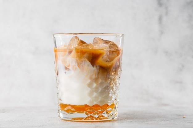 冷たい淹れたてのコーヒーと明るい大理石の背景に分離した牛乳とガラス。俯瞰、コピースペース。カフェメニューの宣伝。コーヒーショップメニュー。縦の写真。
