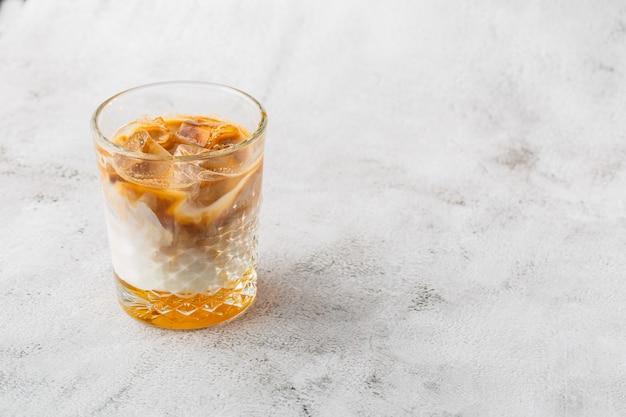 冷たい淹れたてのコーヒーと明るい大理石の背景に分離した牛乳とガラス。俯瞰、コピースペース。カフェメニューの宣伝。コーヒーショップメニュー。横の写真。