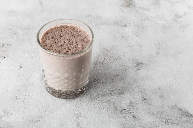 明るい大理石の背景に分離されたアイスココアやチョコレートミルクのガラス。俯瞰、コピースペース。カフェメニューの宣伝。コーヒーショップメニュー。横の写真。
