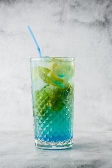 Голубой коктейль с кубиками льда и ломтиками лимона и лайма. голубая лагуна летний коктейль. замороженный голубой лимонад. вид сверху, копирование пространства. реклама для кафе. барное меню. вертикальное фото.