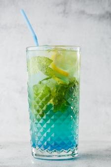 アイスキューブとレモンとライムのスライスと青いカクテル。ブルーラグーンの夏のカクテル。アイスブルーレモネード。俯瞰、コピースペース。カフェの広告。バーメニュー。縦の写真。