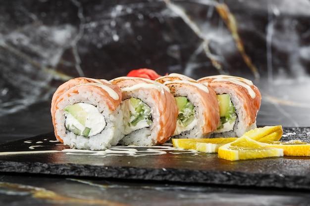 黒い大理石の背景に分離された黒いスレートの上にフレームドサーモン、キュウリ、クリームチーズの巻き寿司。フィラデルフィアロールキュウリの寿司。寿司メニュー。横の写真。