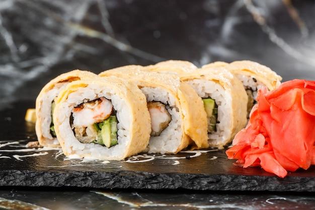黒い大理石の背景に分離された黒いスレートの上にアボカド、ウナギ、キュウリ、クリームチーズの巻き寿司。カリフォルニアロールはオムレツ寿司メニューで覆われています。横の写真。
