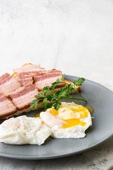 サワー種のトーストにベーコンとポーチドエッグ。白い大理石の背景に分離されました。手作りの料理。おいしい朝食。セレクティブフォーカス。縦の写真。