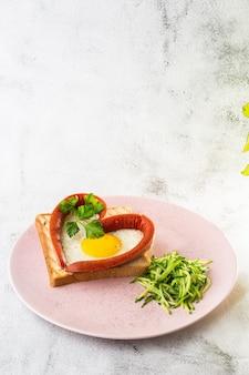 ソーセージと白い皿にハートの形でスクランブルエッグ、白い大理石の背景に分離されたサワー種のトースト。手作りの料理。おいしい朝食。セレクティブフォーカス。縦の写真。