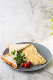 白い大理石の背景に分離されたチーズ、チェリートマト、サワー種のトーストとオムレツ。手作りの料理。おいしい朝食。セレクティブフォーカス。縦の写真。
