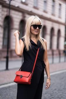 秋のファッション屋外。ファッショナブルなスタイリッシュな黒のオーバーオール、サングラス、建物の背景に赤いバッグのブロンドの女の子。