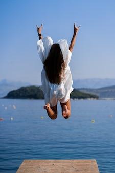 海の景色の背景が付いている桟橋でジャンプ白いドレスの若い美しい女性。休暇中の喜び、安らぎ、自由のコンセプト。女の子は残りを楽しんでいます。自由の概念