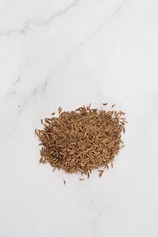 白で隔離される上からキャプチャされたクミンの種子の山。子午線フェンネルおよびペルシャクミンとしても知られるキャラウェイの種子。芳香族駆虫剤。健康と食のコンセプト