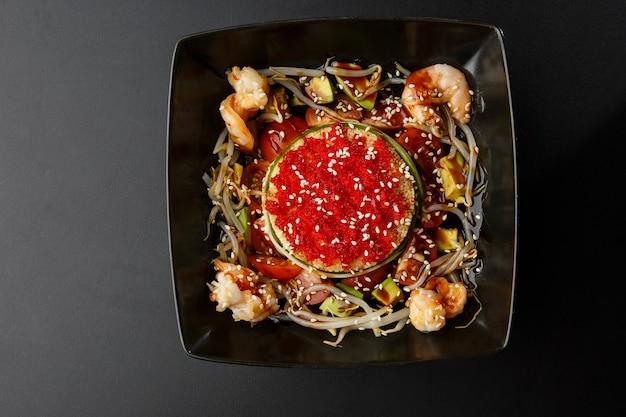 Блюдо кускус с креветками, огурцом, помидорами, ростками пшеницы и красной икрой масаго на тарелке на черном