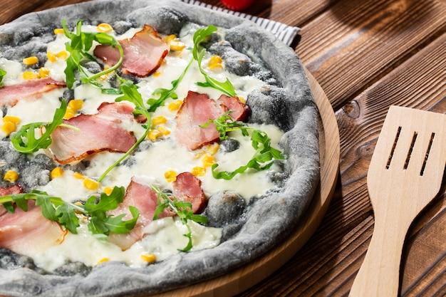 木製のテーブルに美味しいピザの平面図です。ハム、コーン、ルッコラ、チーズのおいしいピザ。黒ピザ。