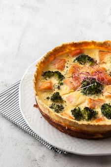 Пирог с заварным кремом, вид сверху. вид сверху. классический пирог с лососем и брокколи из песочного теста с цветочками брокколи и копченым лососем в сливочном крупном плане с яичным кремом на столе.