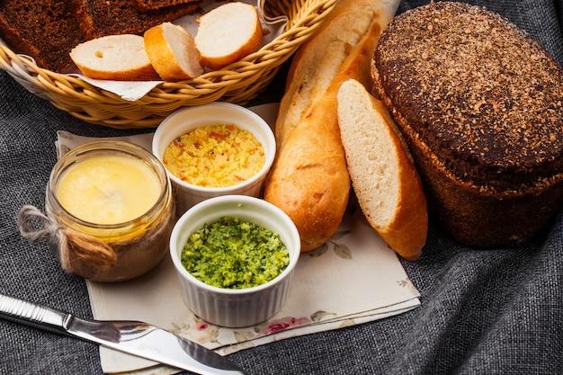 灰色の背景にバターとパン。灰色の背景にバスケットのパン