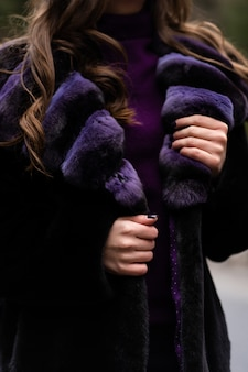 Девушка показывает на камеру стильный свитер, фиолетовый модная шуба.