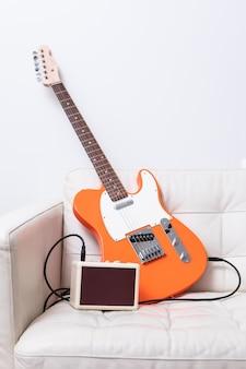 オレンジ色のエレクトリックギターと革張りのアームチェアにケーブル付きアンプ