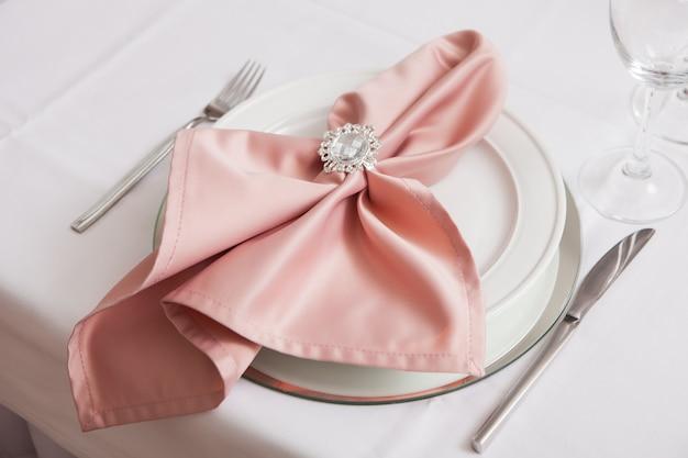 お祝いテーブルにジュエリーで飾られたナプキン付きプレート