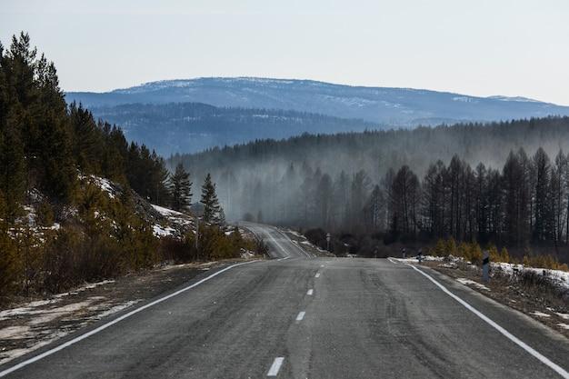 森の上の煙で山の冬の道の眺め。山火事のコンセプト