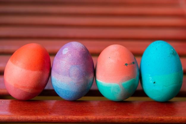 赤い椅子の背景に立っているイースターエッグのセットです。カラフルなお祝いの明るい卵が抽象的に青、ピンク、緑、紫に描かれました。