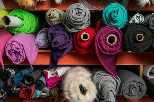 Полки с раскладывающимися рулонами из разноцветной ткани